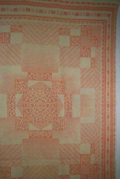 Deken met een geometrisch centraal motief met hoekvullingen en een rand van ca. 20 cm, in zalm en ecru. AaBe