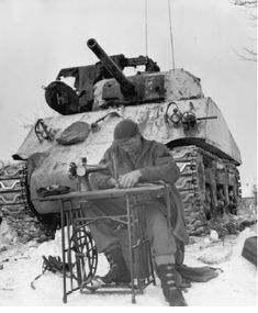 US tank crewman fixing up his clothes on an old sewing machine in front of his tank.