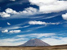 <p>Photo: A volcanic peak jutting up against a blue sky</p>