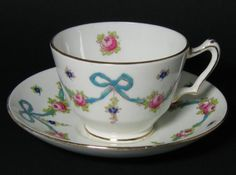 "Vintage Crown Staffordshire Tea Cup.  This beauty has a wonderfully delicate ribbon and bow floral design.  The hand painted blue ribbon is raised to the touch.  The cup measures 2 1/4"" high and 4"" wide.  The saucer measures 5 1/2"" wide, with a smooth round edge.  The backstamp on this piece was used from 1906 - 1930.  The pattern number is F4847. From Grandma Turnbull's collection. $22-56-75USD"