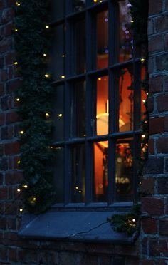 Fairy lights around the window, warm amber light through the night-time window....