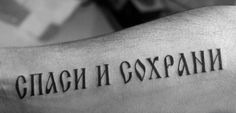 Harsh-lettered russian quote tattoo on arm