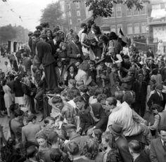 Tweede Wereldoorlog. Bevrijding: de geallieerde troepen worden enthousiast verwelkomd in Amsterdam. Foto: de militairen worden belaagd door het publiek, in het midden een militair met vrouw op schoot, ernaast een militair met een bos bloemen. Amsterdam, Nederland, mei 1945.
