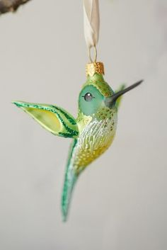 Glittering glass forms this delicate hummingbird to perch on the tree, each one handmade in Germany.