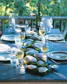 Whether the materials come from your backyard or a garden center, it's easy to incorporate natural elements into the centerpiece of an alfresco dinner. Position stones down the middle of an outdoor table, and intersperse bunches of cushion moss (buy it from a reputable center, as some moss species are protected). Place votive candles along the sides to cast a warm glow over the arrangement.
