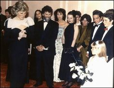 1989-04-16 Diana with Charlie Chaplin's Son, Eugene, and his granddaughter Kiera, who presented her with a bouquet, at a Gala screening of 'City Lights', by Charlie Chaplin, Dominion Theatre, in aid of Birthright and the Royal Academy of Dramatic Arts