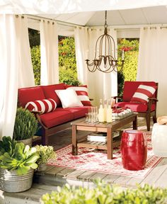 Soft white curtains and red cushions make a vibrant color combination for this covered patio. The chandelier also adds an elegant touch to this fun outdoor space.