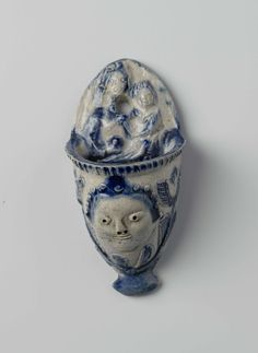 Anonymous | Wijwaterbak, Anonymous, 1750 - 1800 | Wijwaterbak van steengoed. Op de achterplaat versierd met de Madonna met Kind in reliëf. Van voren een mascaron omgeven door bladwerk.