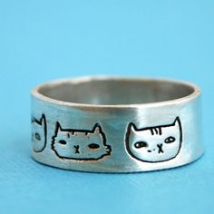 CAT HEADS silver wide ring, illustrated by Gemma Correll, handcrafted by Chocolate and Steel, eco-friendly (small). $61.00, via Etsy.