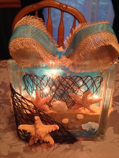 Beach theme glass block with sand, lights, net, and burlap.