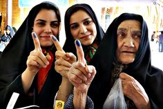 Iranian women show their inked fingers at a polling station during the Iranian presidential elections in the city of Shahre-Ray, Iran.  EPA/ABEDIN TAHERKENAREH