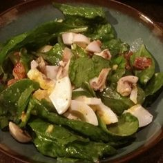 Bermuda Spinach Salad | A smooth, tasty celery seed dressing is whipped up in the blender and poured over the luscious salad fixings - Bermuda onions, chopped spinach, hard boiled eggs, crumbled bacon, mushrooms and a smattering of croutons.