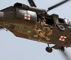 Staff Sgt. Travis Brown, a flight medic assigned to 1st Cavalry Division, and a German soldier assigned to an extrication team lower to the ground with an aircraft hoist while latched on to a jungle penetrator during rescue hoist training. The purpose of the training was to familiarize the extrication team with usage of the aircraft hoist, since insertion via the hoist can often times be the only option into certain austere locations within the mountainous and rugged terrain of Afghanistan…