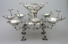 A serving dish of numerous separate bowls attached to one main stem or a type of table centerpiece, usually made of silver, but may be made of any metal or glass or porcelain.