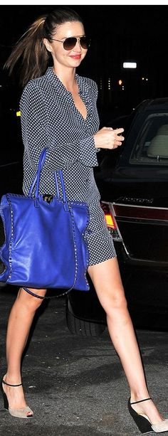 Who made Miranda Kerr's blue studded handbag and white polka dot button down dress that she wore in New York?