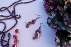 Dark fantasy earrings made with tinted conch shell beads, Swarovski beads and colored wire. These are carefully made and twisted into its on
