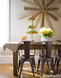 """Designed by Kim Fiscus, this tiny dining room, once an office area, is practical — """"we can hose off the chairs,"""" says Fiscus — with a touch of drama. The 18th-century gilt starburst is six feet in diameter and probably from an Italian church. """"I bought six, and kept the best one.""""   - HouseBeautiful.com"""