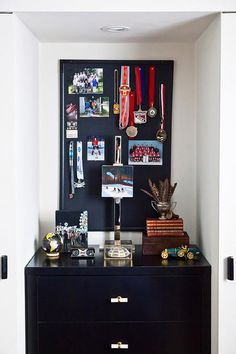 Fabulous boy's closet is filled with a black pin board lined with awards placed over a black dresser finished with a pocket door.