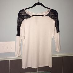 NWOT Mossique White with black lace top NWOT Mossique brand from Bevello boutique. Gorgeous white top with black lace detail on sleeves and shoulders. Cute hole with button closure on the back. Size xs. Super soft and comfy...can be dressed up for a night out or wear during the day. NEVER WORN Perfect brand New condition!! Boutique Tops