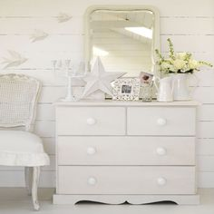 White panelled bedroom with painted chest of drawers and large mirror