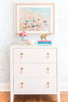 Pink tassel pulls on a tall white dresser brings a trendy finish completing styled stacked books, florals, and a beach illustration wall art. Girl Dresser, Dresser As Nightstand, Tall White Dresser, Animal Print Shop, Fabric Dresser, Headboard With Lights, White Nursery, Girl Nursery, Happy Elephant