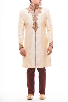 Off White - Beige Silk Brocade pattern sherwani with zardozi work and maroon piping, paired with maroon silk churidaar. Stole sold separately.