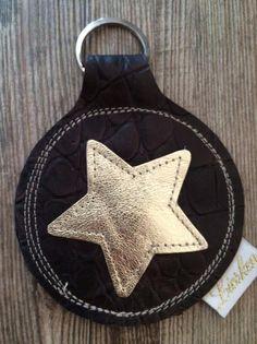 Schlüsselanhänger aus dunkelbraunem Rindsnappaleder mit Kroko-Prägung mit einem goldenen applizierten Stern. Der Durchmesser des Anhängers beträgt 7,5 cm. Inklusive des Ringes hat er eine Länge...