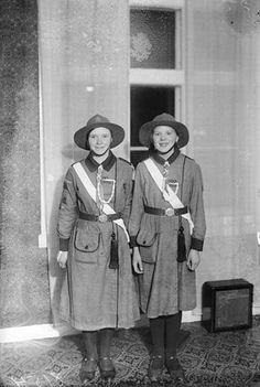 Innostuneena pukujaan esittelevät tytöt seisovat pimeän ikkunan edessä lokakuisena iltana. Heidät on kuvattu Eerikinkatu 31:ssä, missä sijaitsi yksi Pelastusarmeijan kokoushuoneista. Kuvaaja: H. Attila, 1931. TMK