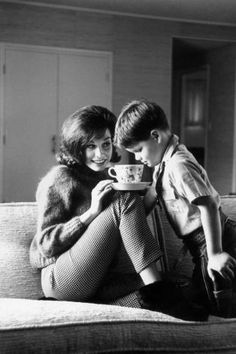 Circa 1965: American actor Mary Tyler Moore holds a cup of tea while her son, Richard, looks inside. Moore is wearing gingham pants and an angora sweater. Richard has a toy gun and holster.