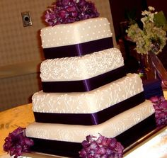 i like the bouquet on top, the real ribbon wrapped around the cake, and the simple, yet elegant and various designs on each cake tier.