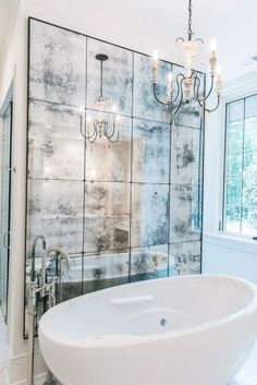 Distressed wall mirror behind BainUltra bathtub. Perfect combination between clean, chic & rustic!