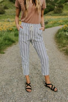 Warm weather is approaching and we found the perfect bottoms to add to your wardrobe this season! The Oslo Drawstring Pant features a blue ivory pinstripe pattern with hidden side pockets. The lightweight material, loose fit, cropped leg provides the comfort style you've been searching for. A paper bag, elastic waist with a drawstring tie creates a flattering silhouette for any figure.