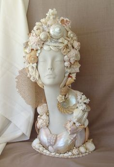 Bust seashell Mannequin head.....this would look great on a bust. We sell mannequin heads at MannequinMadness so you can create centerpieces like this:http://www.mannequinmadness.com/mannequin-heads-wigs/