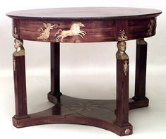 French Empire style Century) mahogany and bronze trimmed round center table with heads and inlaid platform base and black marble top.