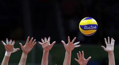 Members of team Russia attempt a block during a women's preliminary volleyball match against Cameroon on August 10, 2016.