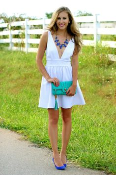 White dress for summer with a tassel clutch and pops of blue.