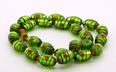 https://vintagelanejewelry.com/collections/shop-all/products/art-glass-green-foil-flower-striped-glass-beads-necklace