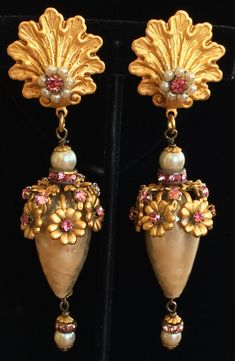 Here is a very rare find of an absolutely gorgeous vintage pair of Miriam Haskell earrings. These earrings are beautifully executed in a very opulent, extra long dangle style with huge lustrous faux baroque pearl drops that are crowned with clusters of gleaming floral gilt filigree and shimmering pink rhinestones.The glistening pearl drops dangle down from earring tops composed of shiny gold tone filigree embellished with creamy faux seed pearls and sparkling pink rhinestones. Lovely…