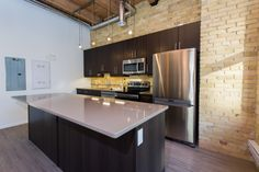 The KINGat District Condos - Loft style conversion condos featuring exposed brick, century old wood beams, 14 ft ceilings and modern finishes. Original brick wall used as character-rich backsplash in modern kitchen with exposed pipes and ducting