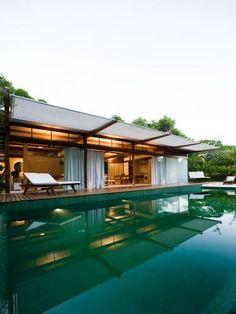 Vista do pavilhão principal, a partir da piscina. As grandes portas de correr envidraçadas transformam o living em uma grande varanda