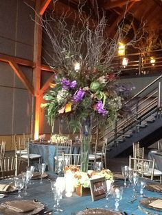 Amazing tall wedding centerpieces of green, gold, and purple. Curly willow, artichokes, purple stock, hanging green amaranthus, antique green hydrangea, mango calla lilies, and oak leaves.