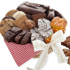 Snack Gift Basket - Medium    Every occasion is complete with a yummy bakery assortment of freshly baked cakes and cookies! We've included mini tea cakes and a loaf cake, rich chocolate truffles, chewy brownies, crunchy chocolate chip cookies and gourmet cookies complete with a gingham napkin. Choose your message ribbon. 27 pieces.  $49.99