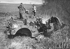 Former GI Ernest Kreiling and his bride looking at a wrecked jeep during tour of battlefields. France - April 1947