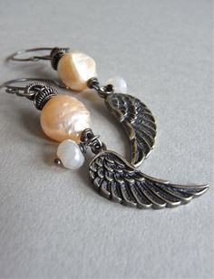 The Take Flight earrings - irregular peach hued druzy pearls are paired with sterling angel wings and teensy pearlised chalcedony rondelles. Ornate wire wrapping leads to my signature ear wires in sterling.