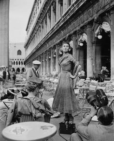 A model wearing Christian Dior fashions being filmed at a cafe on the Piazza San Marco in Venice,1951.