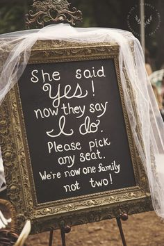 """""""She said yes! Now they say I do. Please pick any seat. We're now one family, not two!"""" Framed chalkboard sign for the wedding ceremony."""