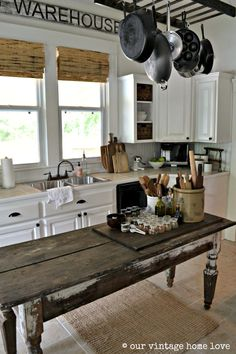 Farmhouse Country Kitchen Ideas - great post that proves it doesn't have to cost a fortune to have your dream home!  Here, a farmhouse table is used as an island and an old ladder serves as a pot rack - if you're short on space, this is the perfect place to store your pots.