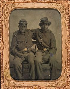 Two unidentified African American Union Army soldiers, full-length portrait,  wearing uniforms, seated with arms around each other's shoulders,  c. 1864