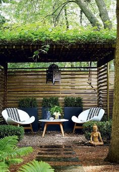Zen garden features a pergola over a pair of white modern chairs and outdoor accent table placed before three black planters.