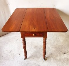 552: Antique Pine Drop Leaf Table with Maple Drawer, Elaborately Carved Legs on Casters $350